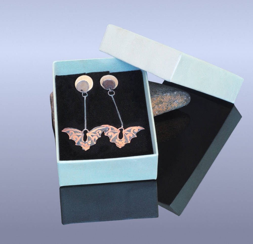 Copper and silver flying bats earrings in a box