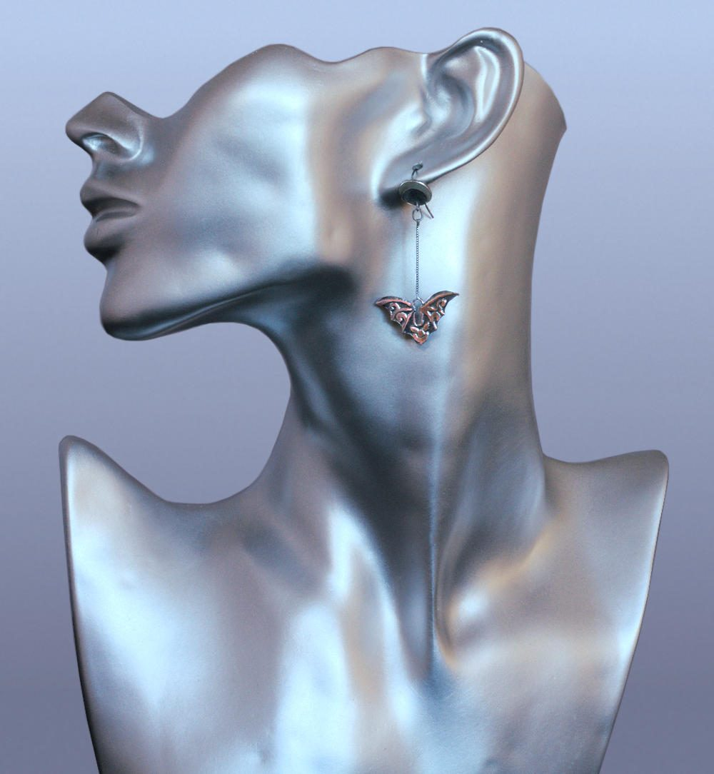 Flying bat earring shown on a display bust