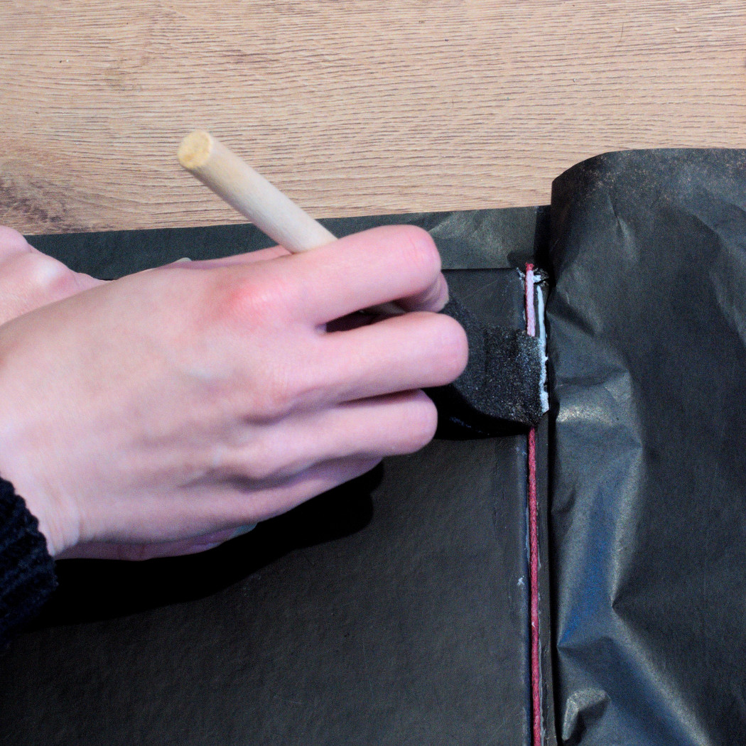 glue being put in the crease of a back cover of a sketchbook with a foam brush